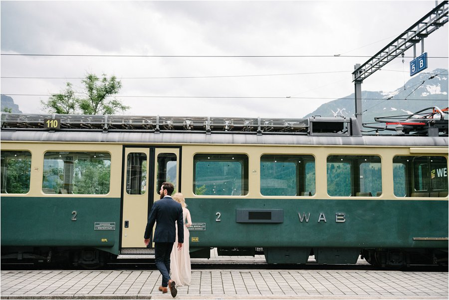Bride and groom walk to the train from Wengen - After wedding honeymoon shoot in Wengen by Caroline Hancox Photography