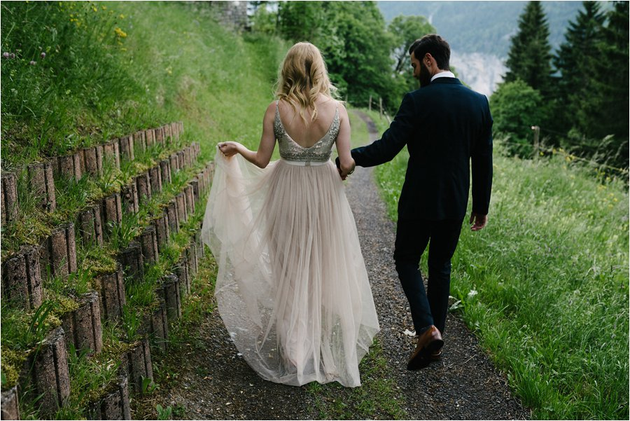 Bride and groom walk down a dirt path - After wedding honeymoon shoot in Wengen by Caroline Hancox Photography