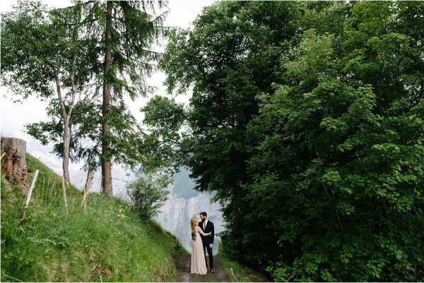 Bride and groom stand and embrace under a tree - After wedding honeymoon shoot in Wengen by Caroline Hancox Photography