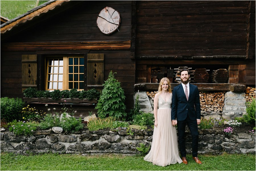 Bride and groom standing in front of a wooden chalet in Switzerland - After wedding honeymoon shoot in Wengen by Caroline Hancox Photography
