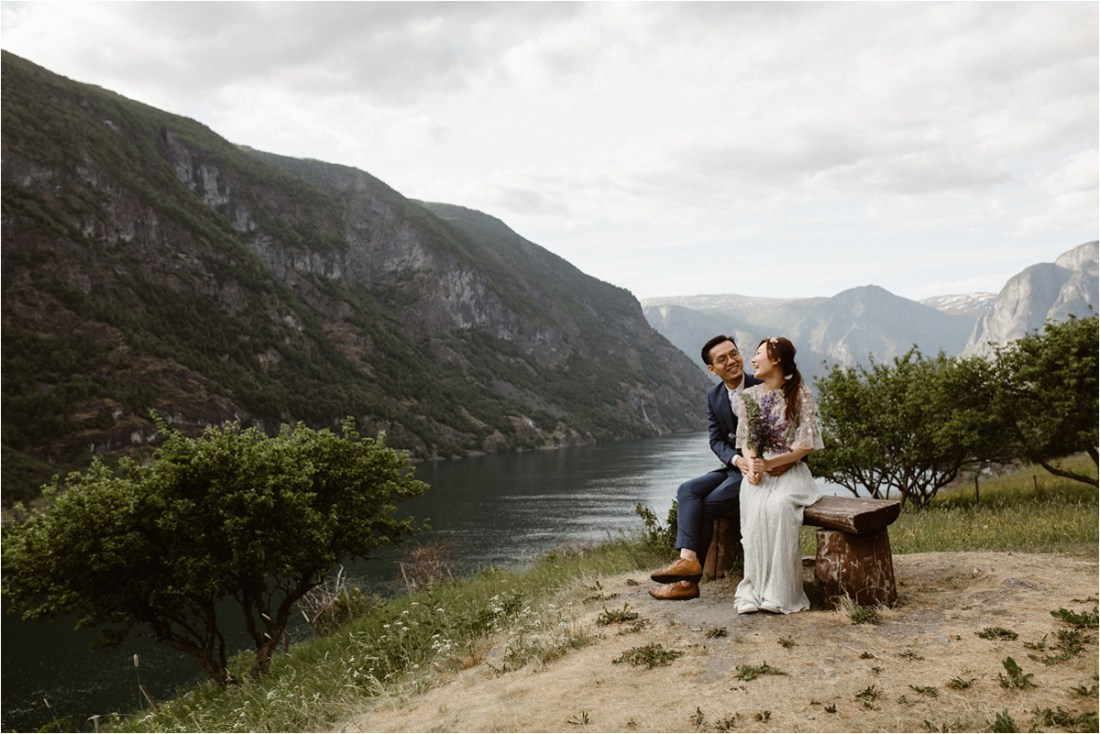 Bride & Groom sitting on a wooden bench by Sognefjorden by Ingvild Kolnes