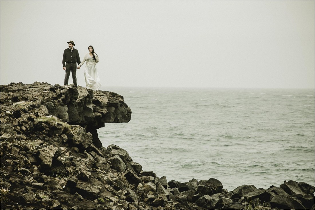 Gaby & German stand on the edge of the cliffs for an anniversary shoot in Iceland by Projectphoto.ch