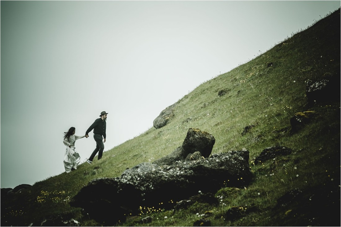 Gaby & German hike up a hillside for their Iceland anniversary shoot by Projectphoto.ch