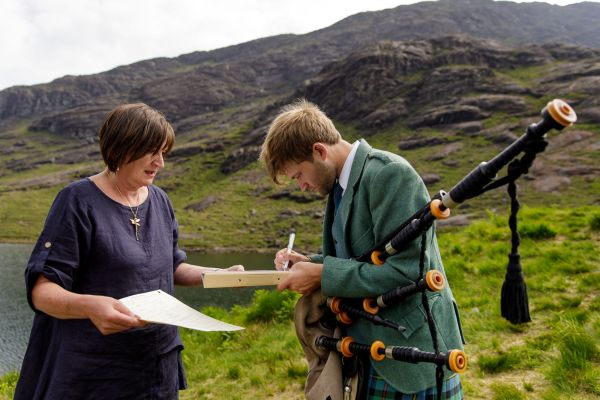 The bagpipe player signs the wedding certificate by Lynne Kennedy Photography