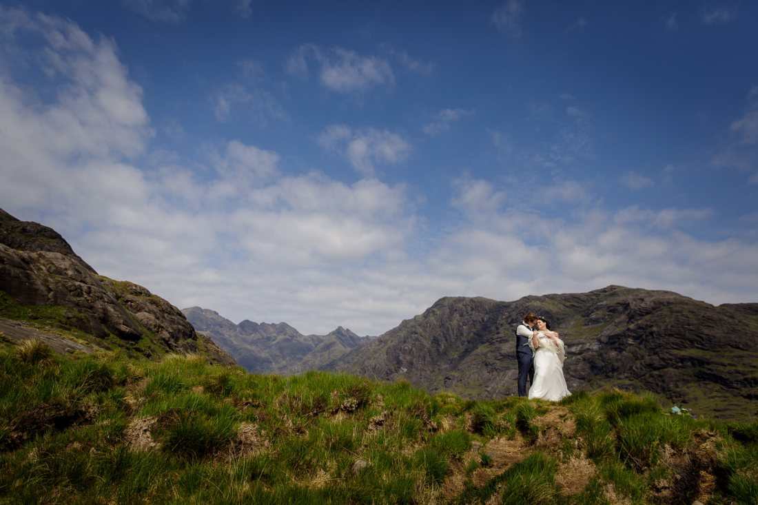 Jürgen embraces Tina with the Scottish mountains in the background by Lynne Kennedy Photography