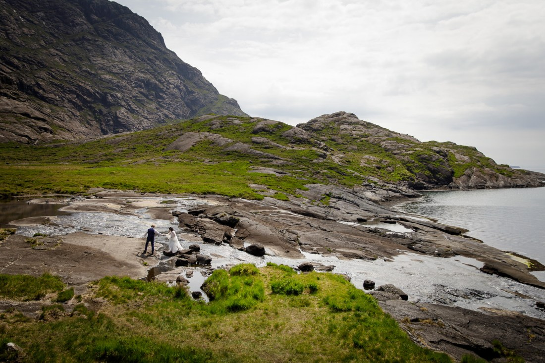 Tina & Jürgen walk along a riverside on the Isle of Skye by Lynne Kennedy Photography