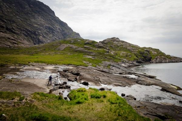 Tina & Jürgen walk along a riverside on the Isle of Skye by Lynne Kennedy Photography