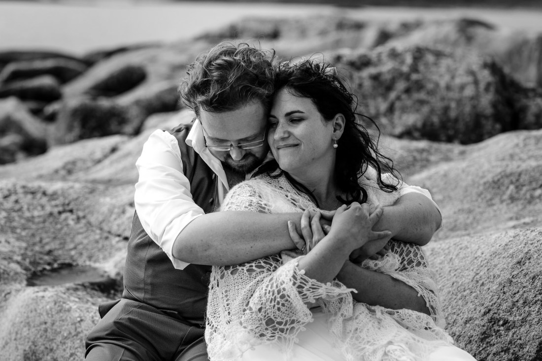 Black & white close up photo of Tina & Jürgen embracing on some rocks by the shores of the Loch by Lynne Kennedy Photography