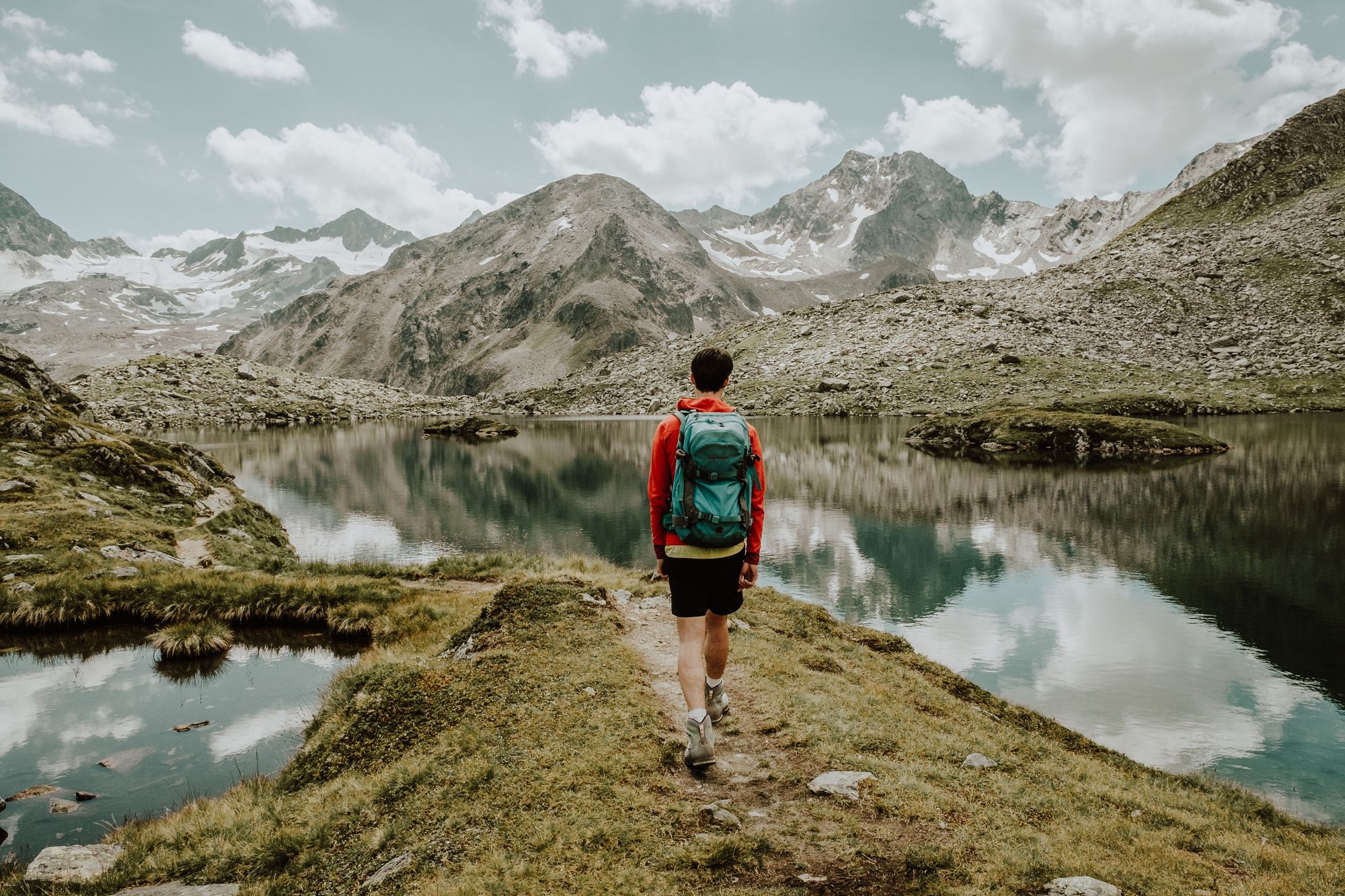 Hiking the Stubai High Trail, a hiker walks between two mountain lakes in the Austrian Alps, on one of Europe's best multi-day hiking routes. Image by Wild Connections Photography