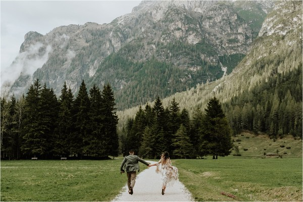 Christina & Ted run down a mountain trail in the Dolomites by Wild Connections Photography