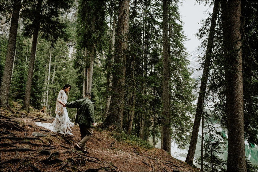 Ted leads Christina through the pine forest at Lago Di Braies in the Dolomites by Wild Connections Photography