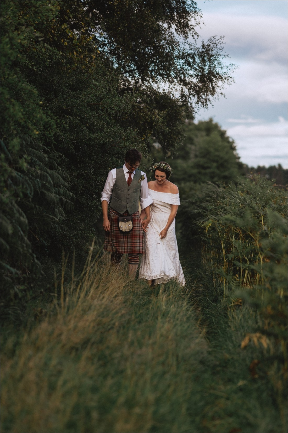 Bride and groom walking through the long grass by Fox & Bear Photography