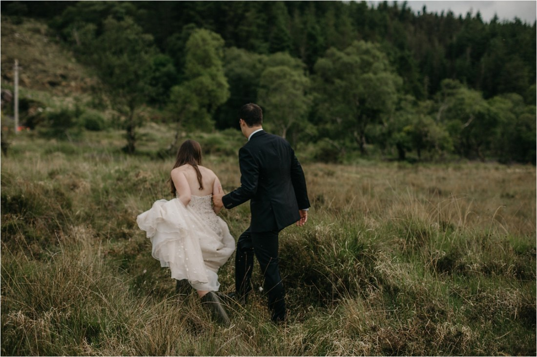 The bride and groom walk through long grass in County Galway in Ireland by No Other Love Photography