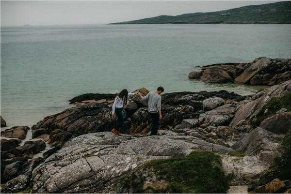 Couple hikes over rocks by the beach for their pre-wedding shoot in Ireland by No Other Love Photography