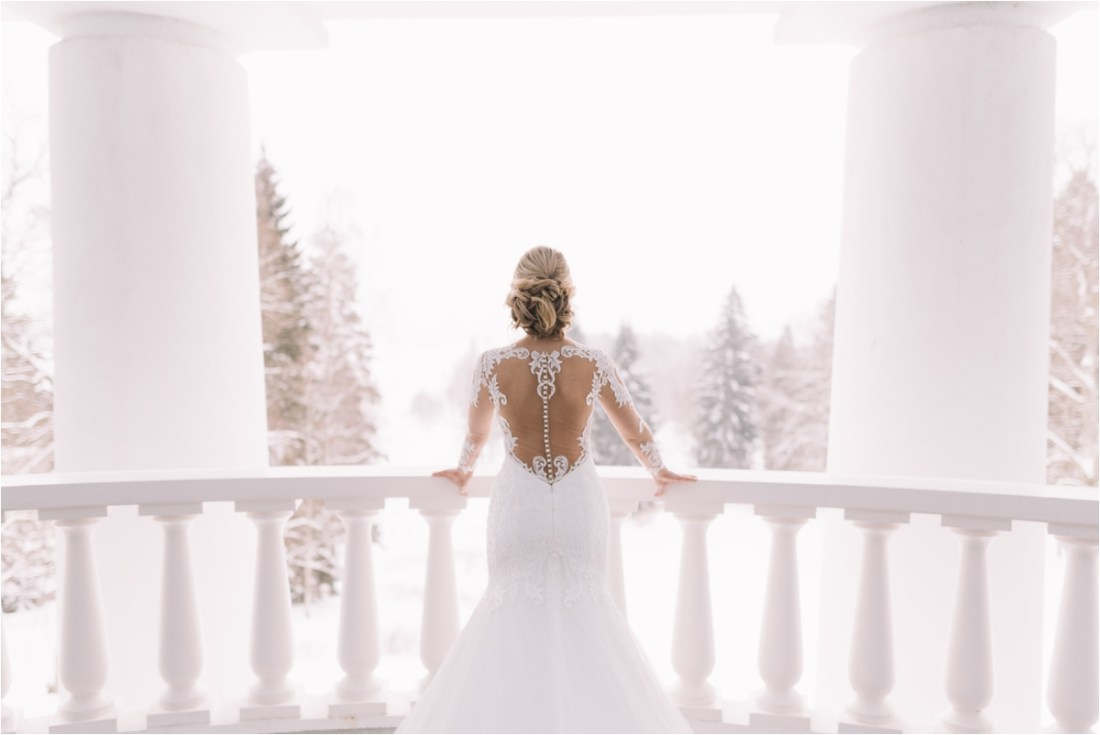 The bride looks across a snowy landscape from her hotel balcony by Lucie Watson Photography