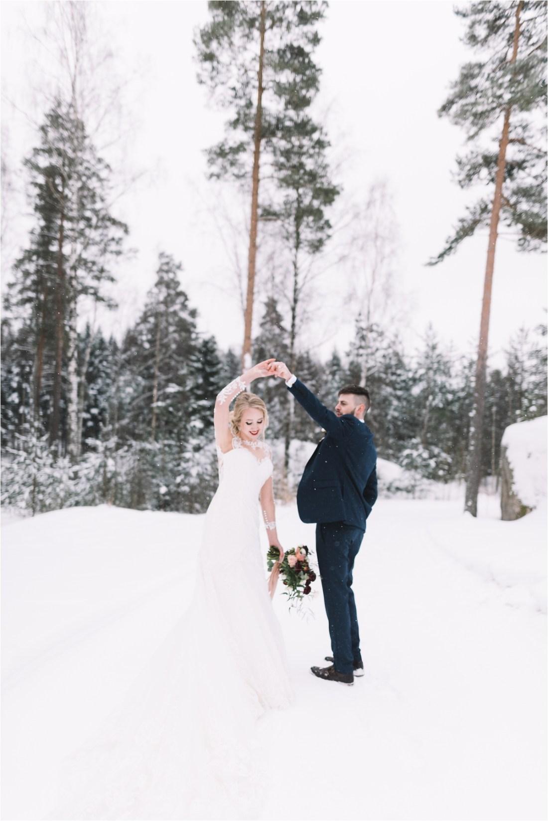 The bride and groom dance in the snow in Finland by Lucie Watson Photography