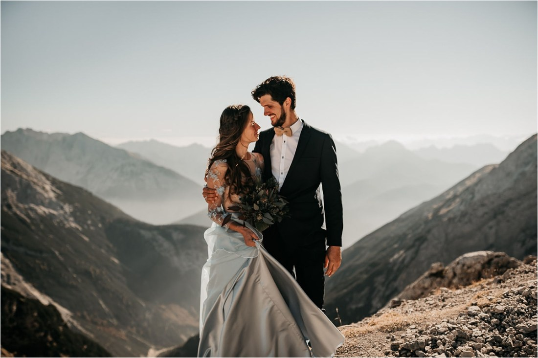 Bride and groom turn to face each other at the top of the Karwendalbahn in Mittenwald by Aneta Lehotska