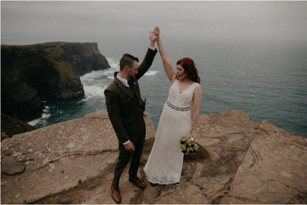 Cliff top Hand fasting of Jon and Sara, on the Cliffs of Moher, Co Clare, Ireland Captured by Photographers Seandkate the bride and groom raise their arms in celebration