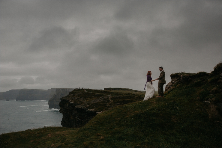 Cliff top Hand fasting of Jon and Sara, on the Cliffs of Moher, Co Clare, Ireland Captured by Photographers Seandkate Jon & Sara climb up a hill with a view of the cliffs of Moher and ocean behind them