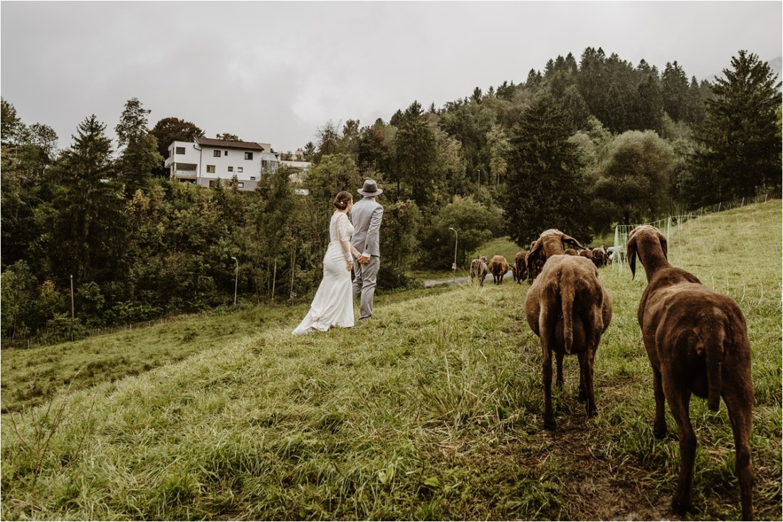 Bride and groom walk through a field of sheep after their Innsbruck elopement in Austria. Photos by Wild Connections Photography