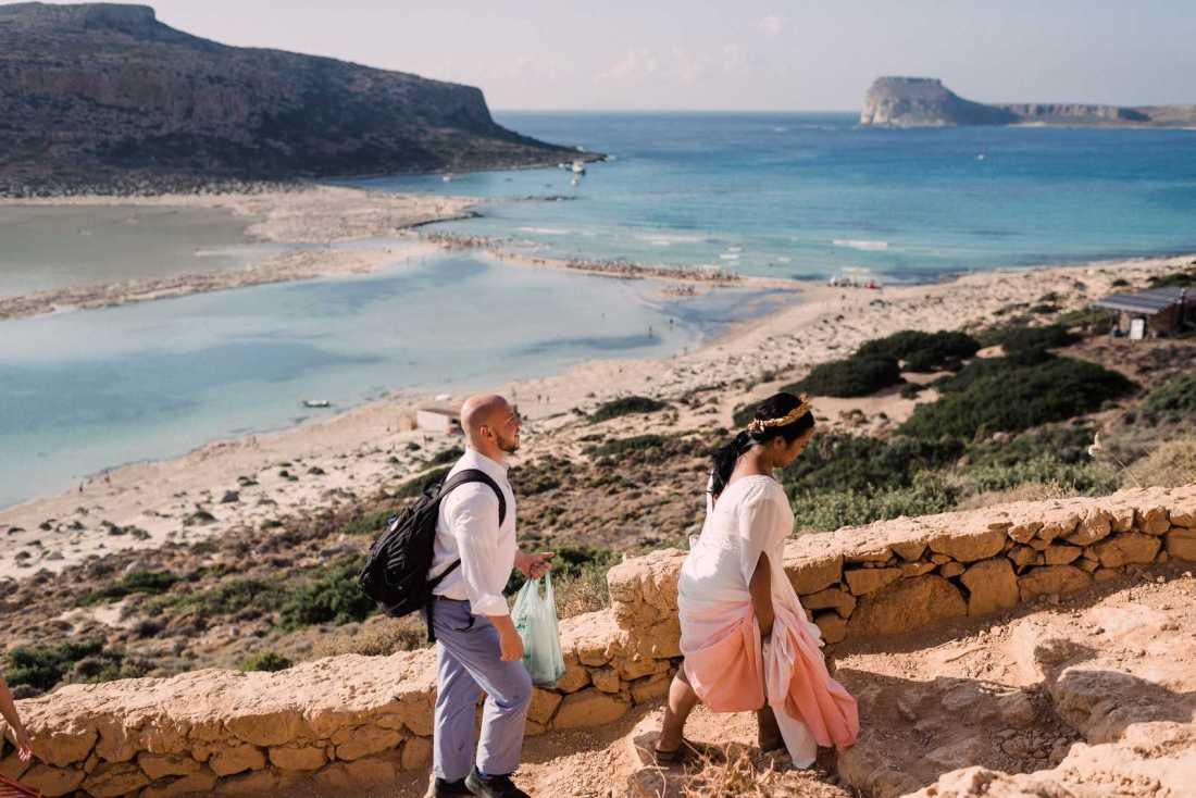 Bride and groom hiking to Balos