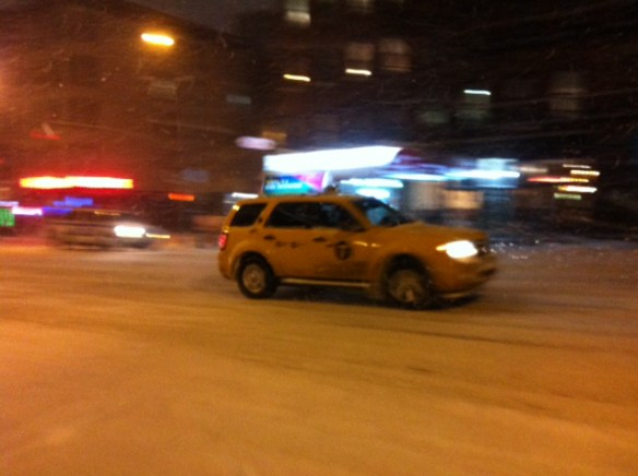 NYC taxi making its way through heavy snowfall.