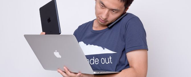 iPhoneとiPadminiとMacbook Airを使う男性