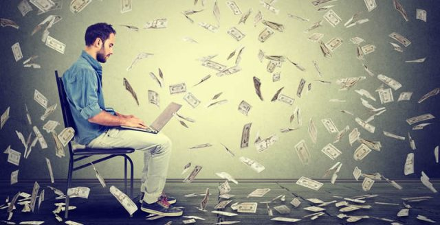 Man working on laptop with money raining down