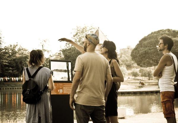 Un groupe de visiteurs en train de découvrir l'histoire et la construction du lac devant le second panneau.