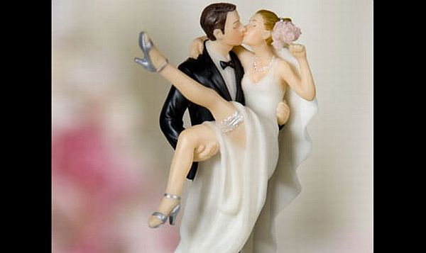 Holding up and kissing wedding cake topper
