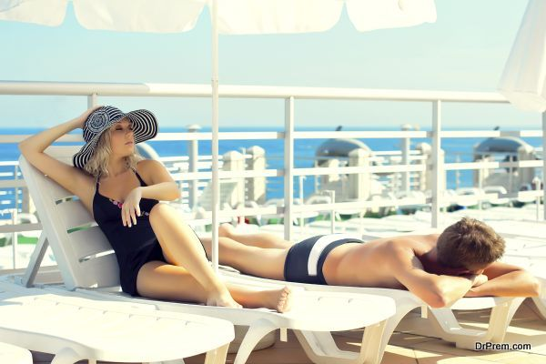 Man and woman lying on chaise lounges on a yacht in the ocean