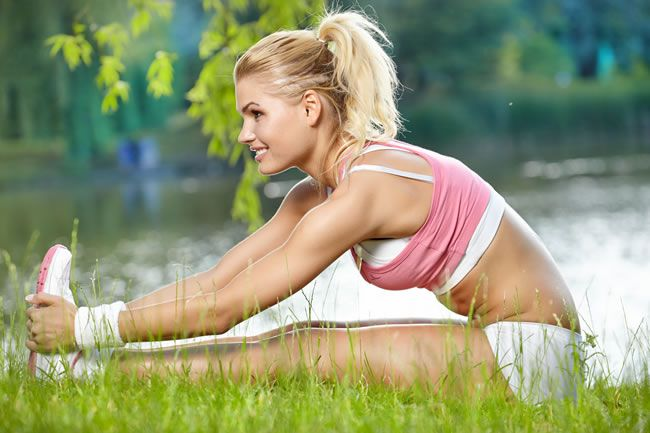 woman stretching in park 10 Tips for Keeping fit Over the Festive Season