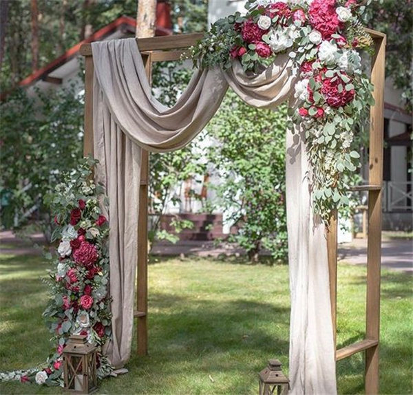 Beautiful wedding ceremony backdrop arbor with draping, flowers and lantern accents