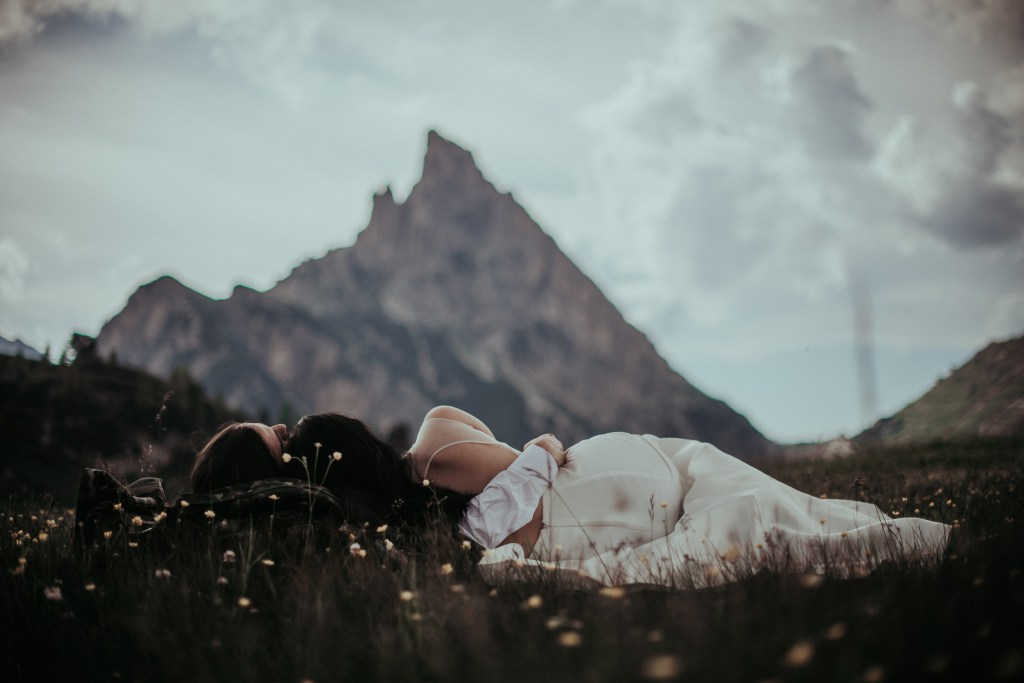 Intimate Wedding In the Dolomites - Luxury Wedding - Couple Laying in the meadows of Alta Badia