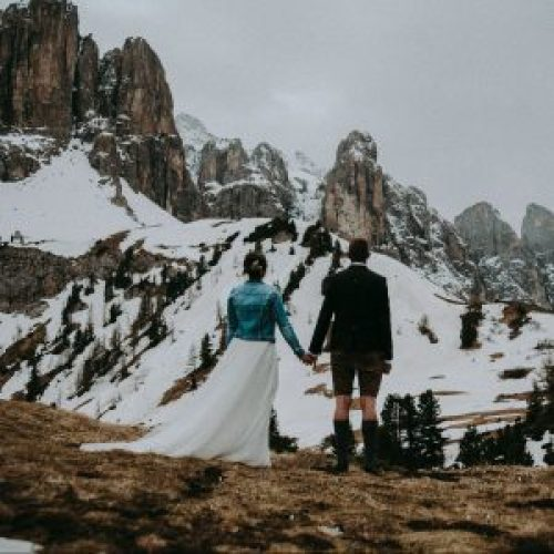 Wedding Couple Looking At The Snowy Mountains Holding Hands Alta Badia Dolomites Italy