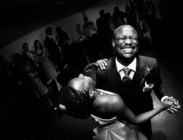Bride and groom dancing with big smiles