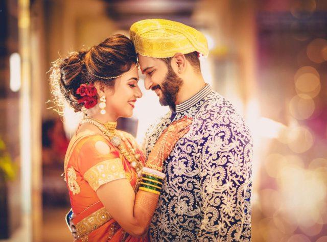 bride and groom in colour coordinated maharashtrian wedding wear beautiful Maharashtrian couple in orange sari and blue sherwani