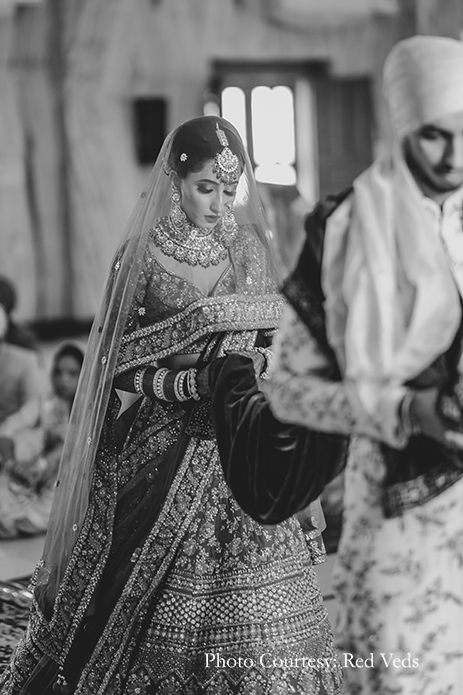 Bride in red lehenga with elaborate polki jewelry and Groom in a white floral sherwani with an emerald green shawl and a multilayered necklace
