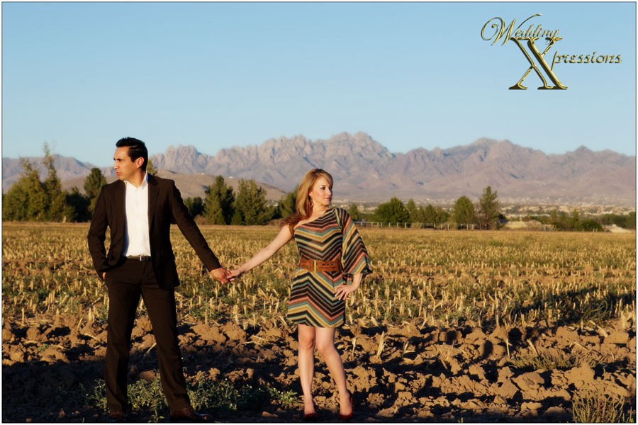 las cruces mountain behing engaged couple