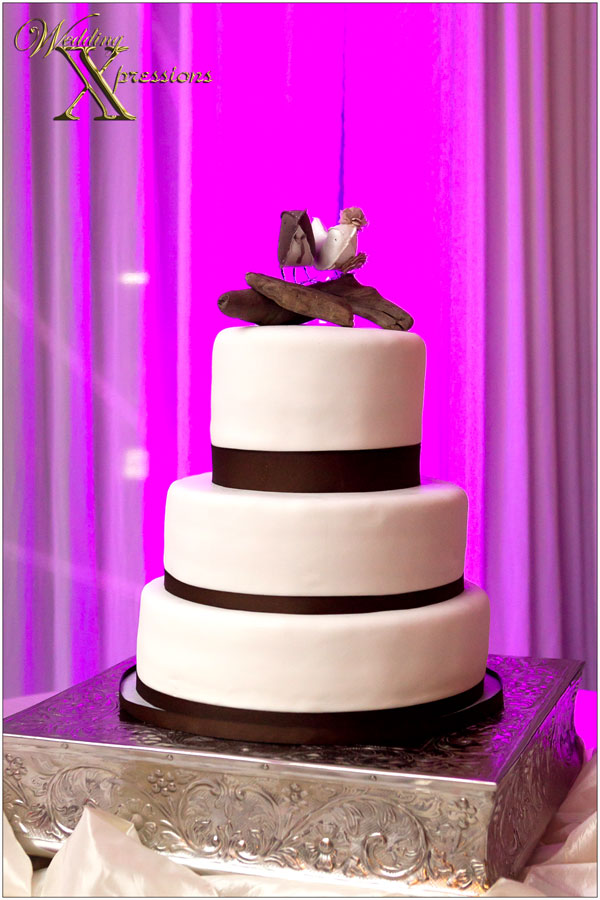 white and brown wedding cake with love birds topper