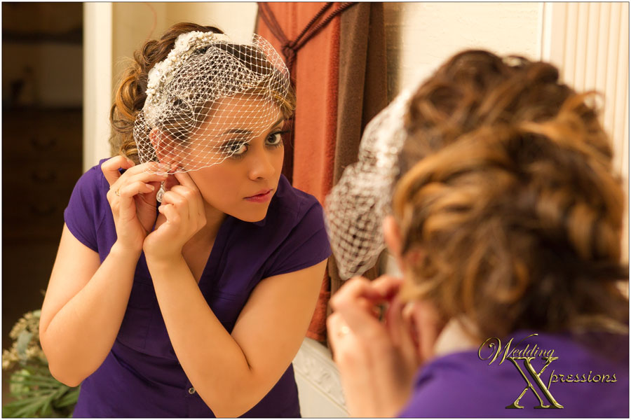 bride with small veil putting on earring