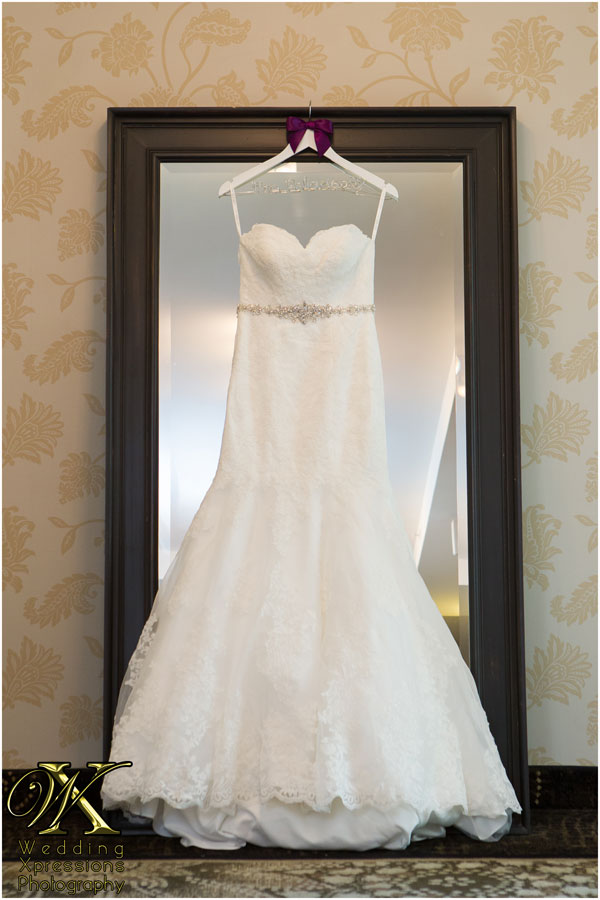 white wedding dress hanging on mirror