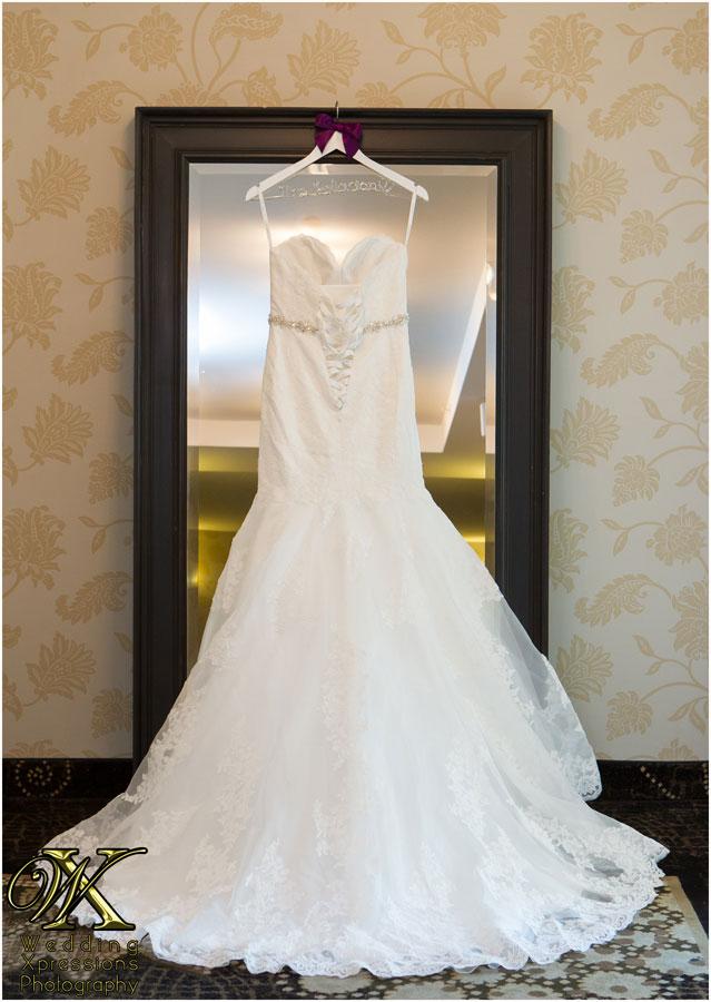 back of white wedding dress hanging on mirror