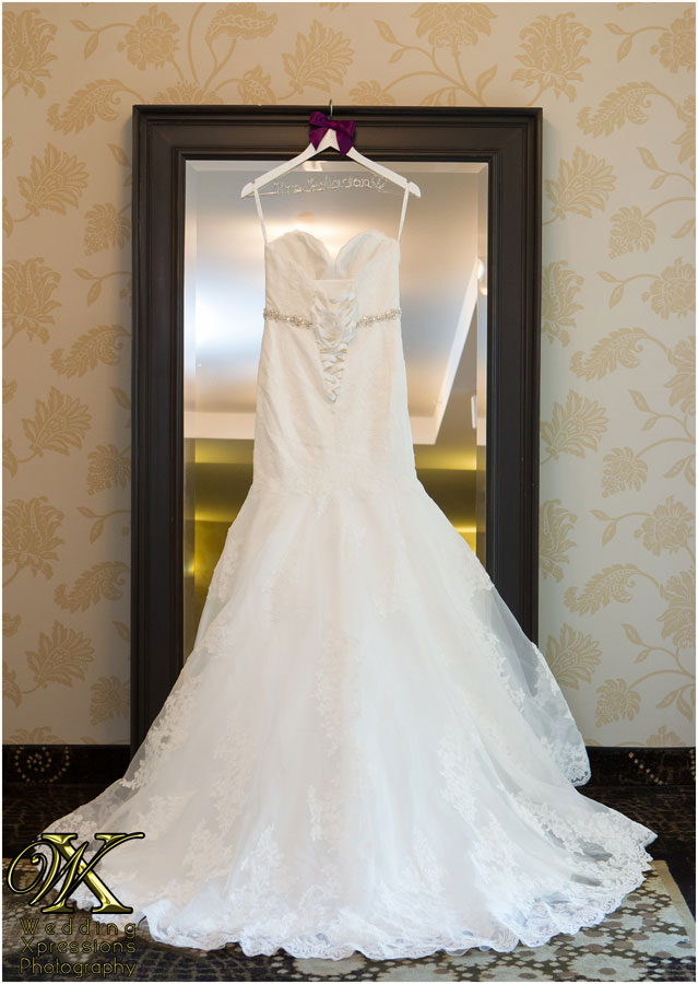 back of white wedding dress hanging on mirror
