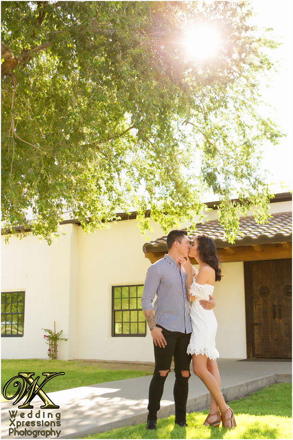 engagement session couple with tree rustic building sun shining