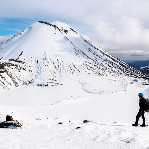 Person standing in the snow on the Adrift Tongariro Winter Crossing in front of mt Ngauruhoe Tongariro National Park New Zealand