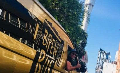 golden auckland brewbus vehicle in front of sky tower auckland