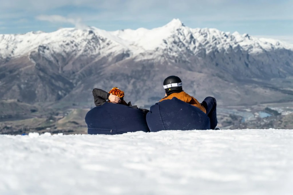 Couple in ski gear sitting on bean bags in the snow at Coronet Peak Queenstown, looking at the mountain range in the distance
