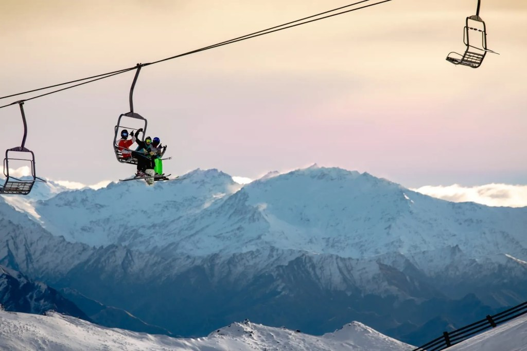 people waving from the chair lift at the remarkables ski field in queenstown at dawn