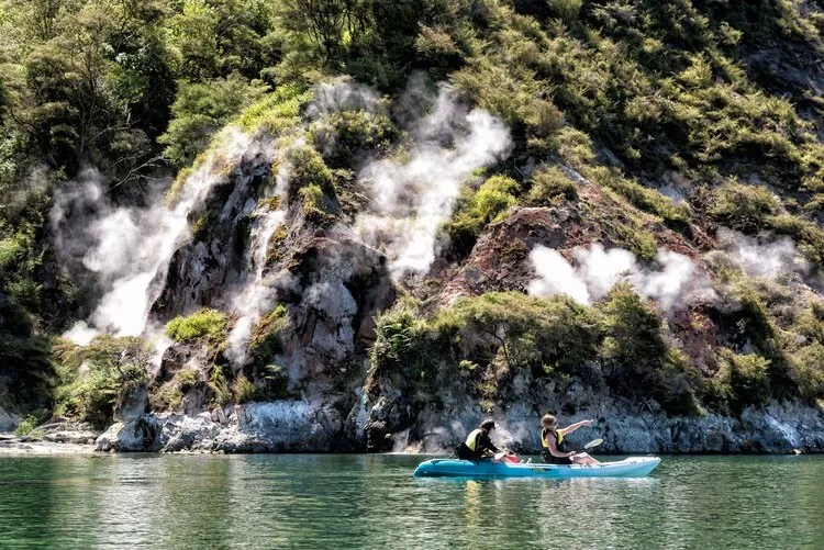 A pair of kayakers in front of the steaming cliffs on lake rotomahana, tour by paddle board rotorua